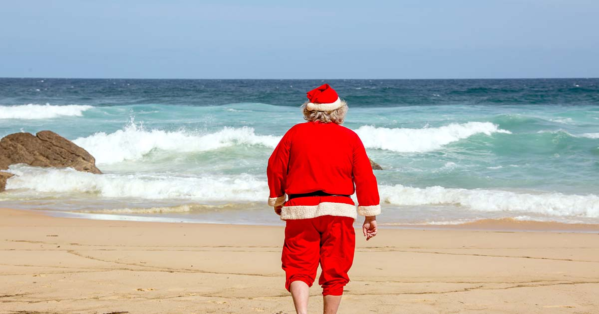 Santa walking on the beach towards the ocean