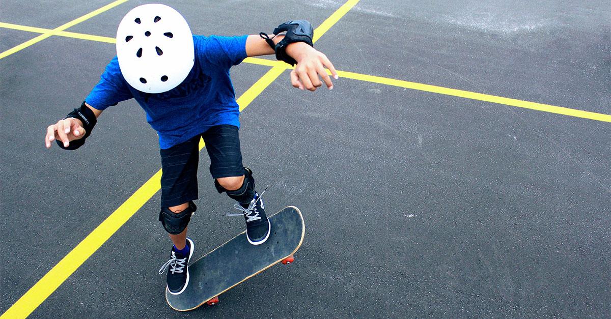Boy wearing helmet learning to skateboard