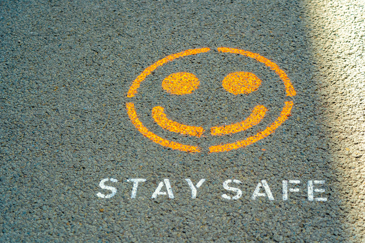 Happy face with Stay Safe text spray painted on asphalt