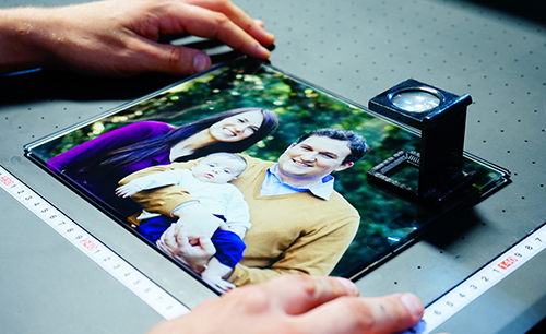 Hands carefully reviewing colorful family portrait