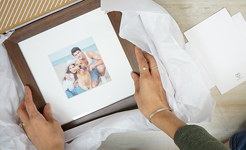Opening gift box with beautifully framed family portrait