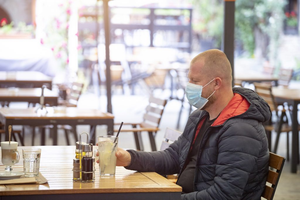 Man sitting separated in restaurant wearing medical protective face to protect infection from coronavirus covid-19, restaurant and social distancing concept