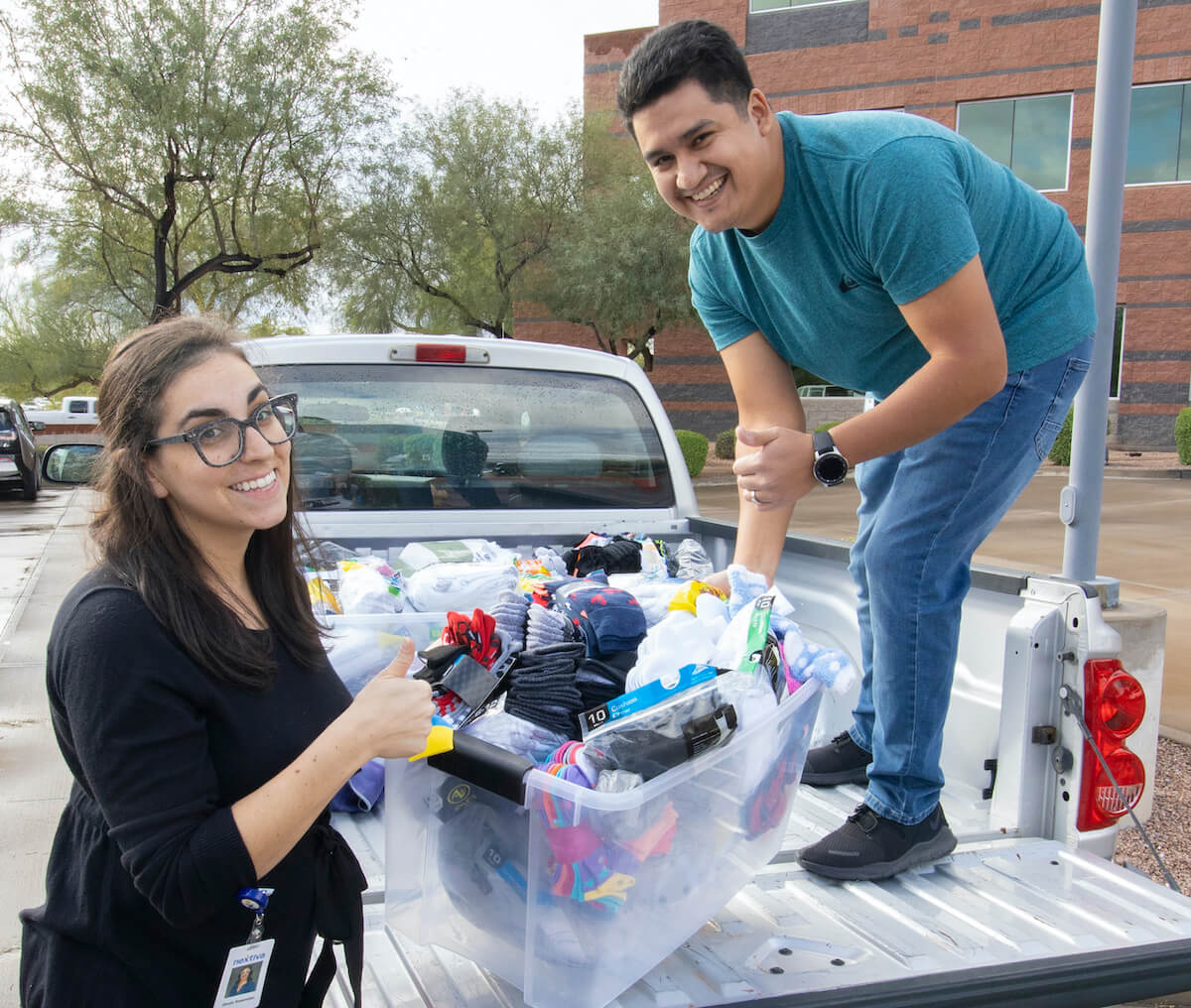 Shula Resendez and Andrew Ruiz loading up more than a thousand pairs of socks into a pickup truck.