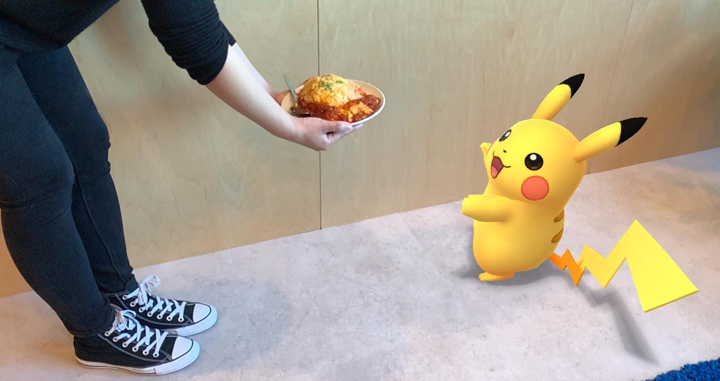 AR snapshot showing a person handing a dish to Pikachu
