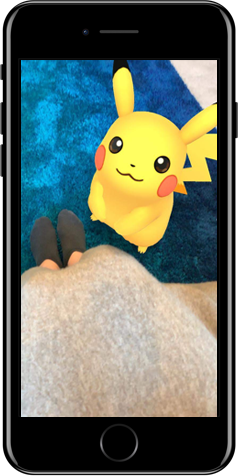 iPhone showing in-game AR feature. Pikachu is looking up at the trainer