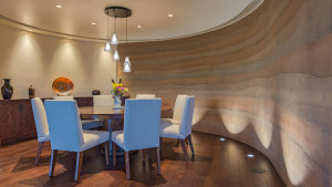 Dining area shaped by interior face of rammed earth wall.