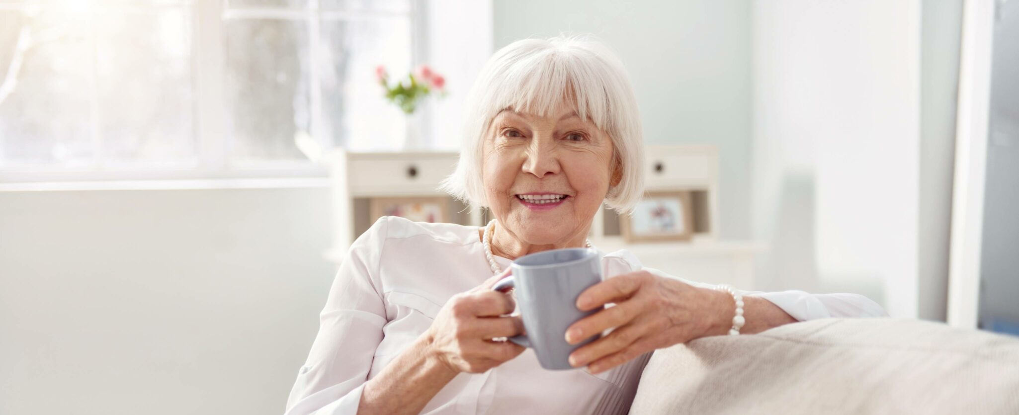 senior lady relaxing on a couch while drinking coffee