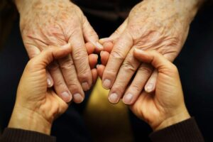 A young person holds an older persons hand in comfort