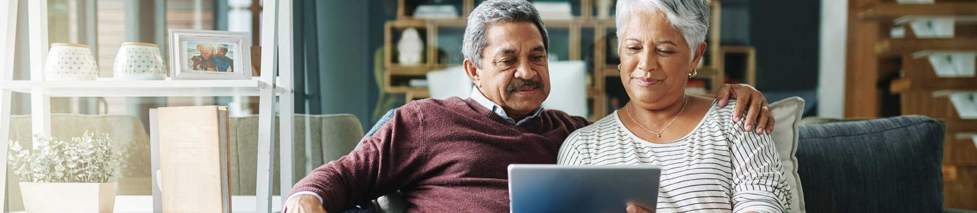 A senior couple sitting on a couch and looking at a laptop