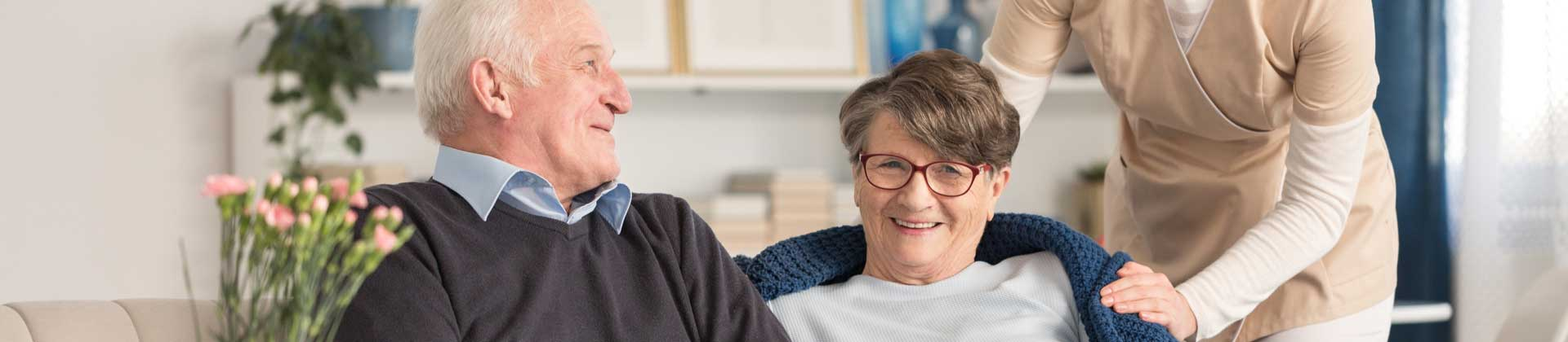 A senior couple sitting and looking toward the camera while a nurse stands behind them