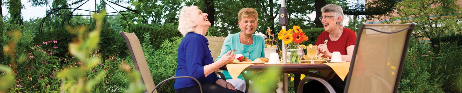 A group of senior women sitting at table outdoors enjoying a meal