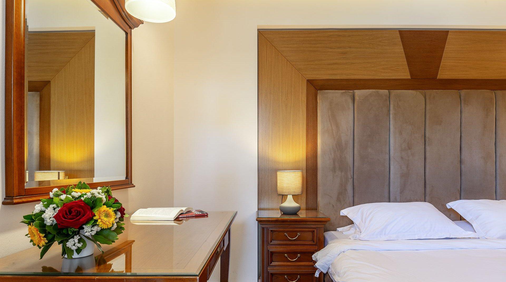 Το κρεβάτι του δωματίου με το γραφείο και τον καθρέφτη