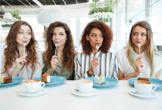 Four female friends eating cake