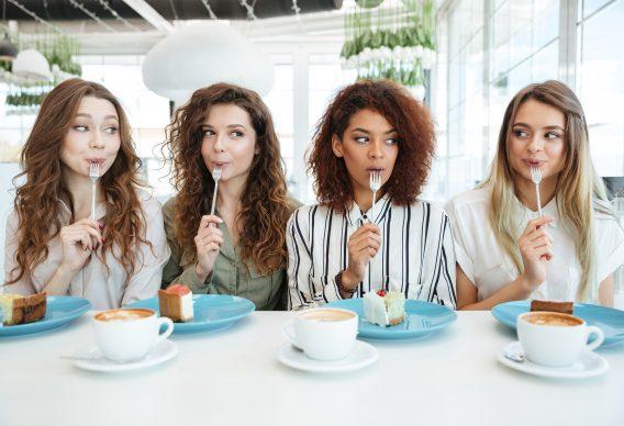 Four female friends eating cake