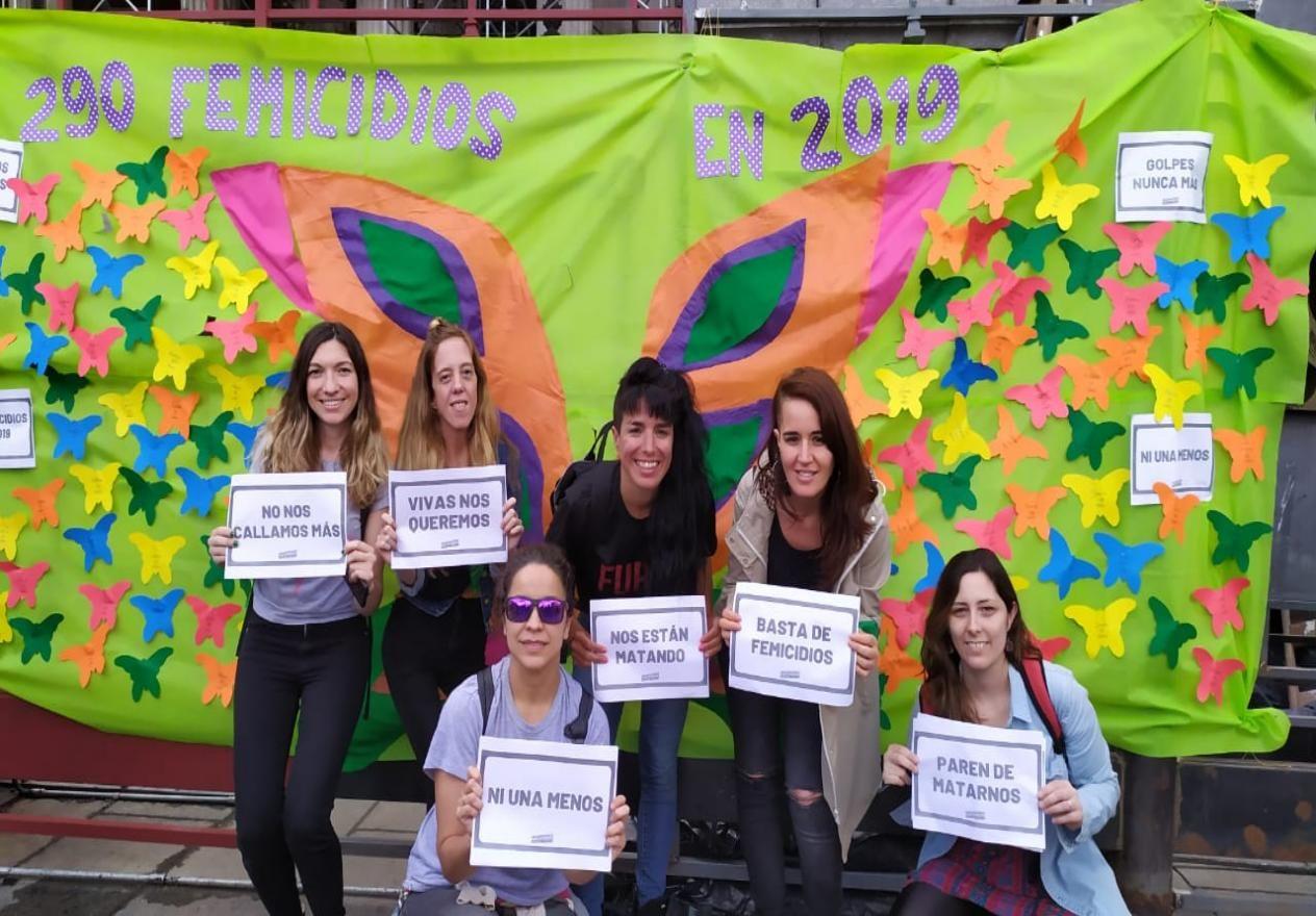 Equipo del observatorio con carteles: Basta de femicidios, Paren de Matarnos, No nos callamos mas