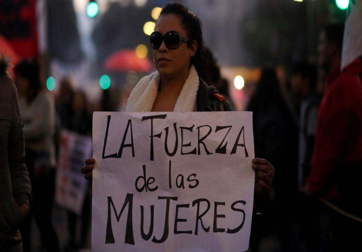 mujer sosteniendo cartel que dice La Fuerza de las Mujeres