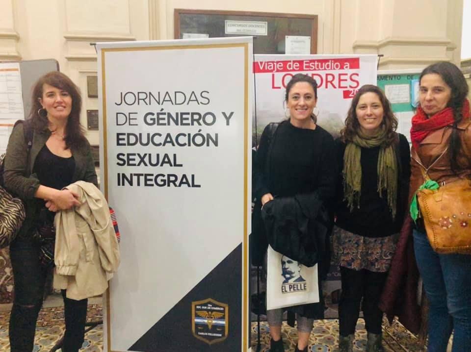 Cris, Raqui, Lau y Agus al lado del cartel del Pellegrini en las jornadas de género y ESI