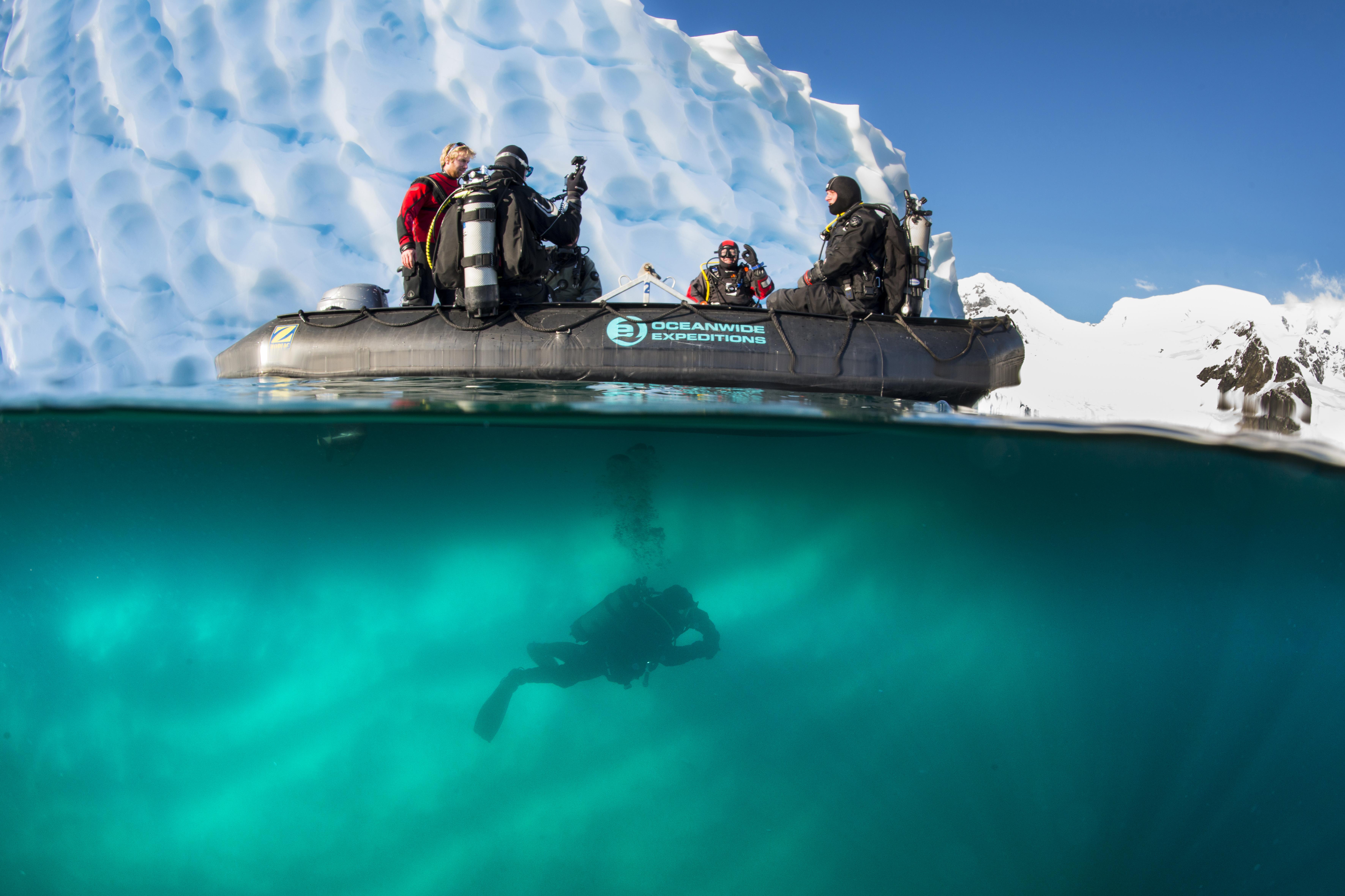 Polar Diving, zodiac in front of iceberg, diver diving under zodiac, Antarctica