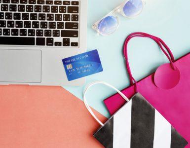 Foto de cima mostrando o teclado de um, cartão de crédito, óculos de sol e bolsas.