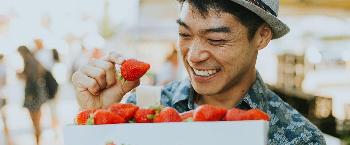 cliente comprando morangos sorrindo tendo uma ótima experiência