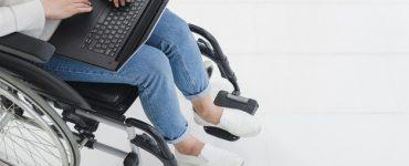 Mulher sentada em cadeira de rodas com laptop no colo trabalhando