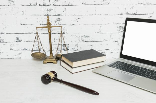 mesa com livros de direito, martelo de juíz e balança