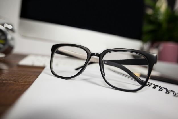 óculos em cima de um caderno