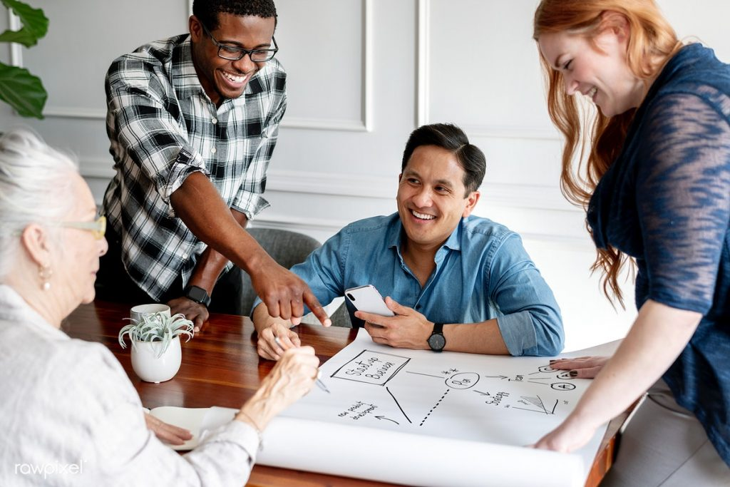 4 pessoas sorrindo e conversando sobre gerenciamento de projetos