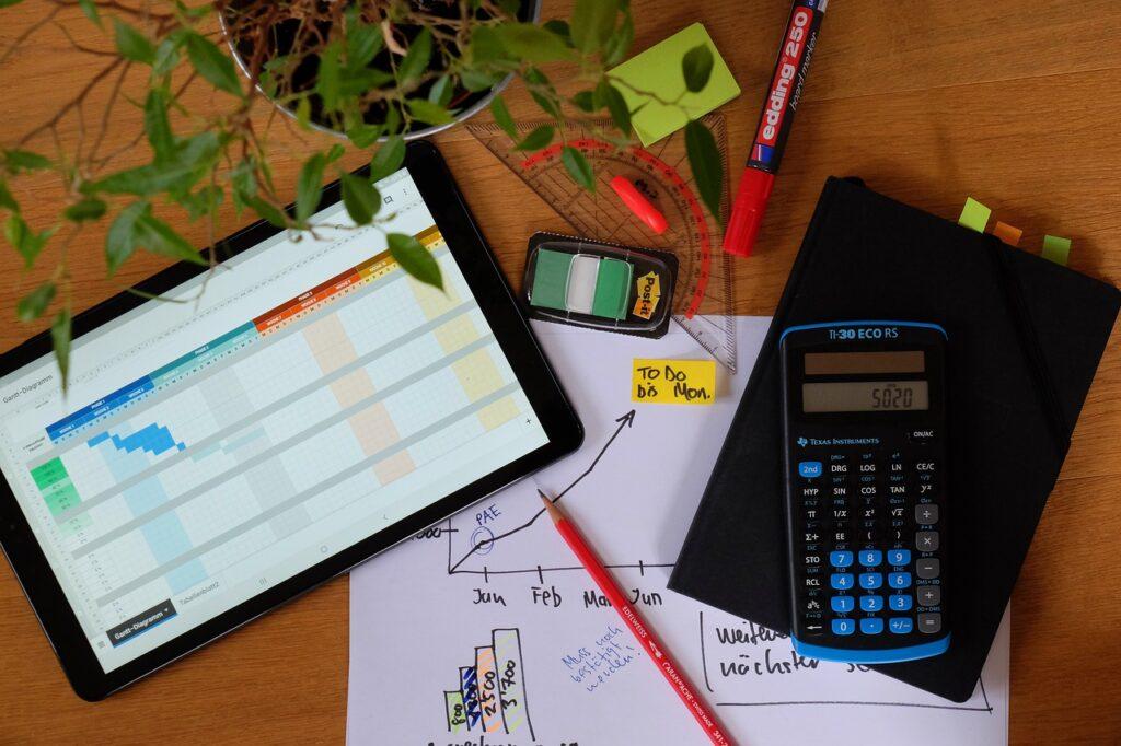 Uma mesa com calculadora, agenda, planner, algumas réguas e papel descrevendo processos de gerenciamento de projetos