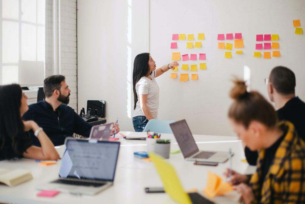 A imagem retrata uma sala com 5 pessoas, onde 1 está em pé falando sobre gestão de projetos e com adesivos coloridos colados em um quadro branco.