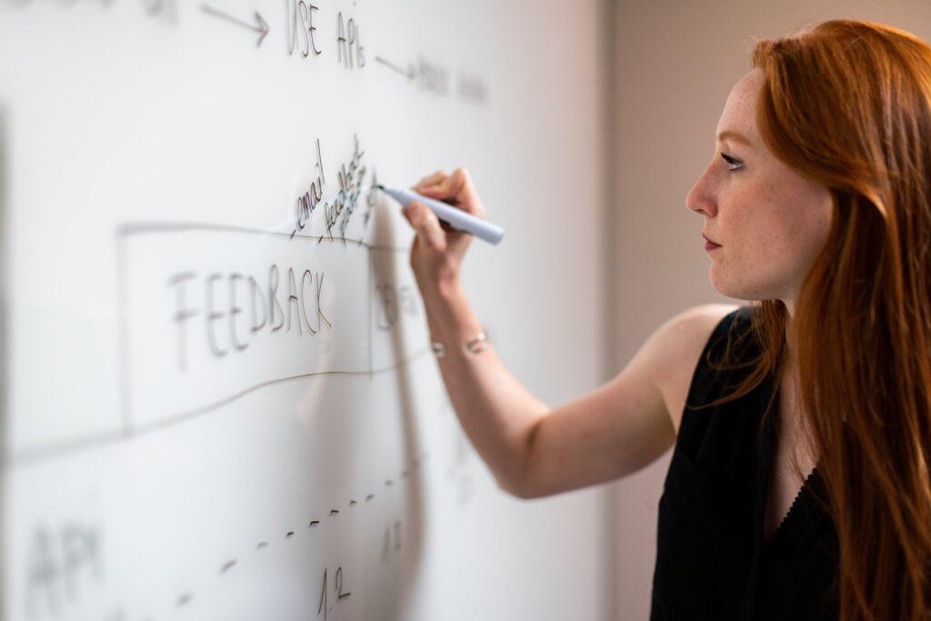 A imagem retrata uma mulher ruiva escrevendo sobre gestão de projetos e Feedback em um quadro branco com uma caneta preta.