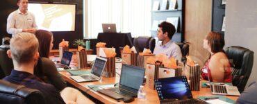 Reunião em uma mesa grande com várias pessoas falando sobre gestão de pessoas