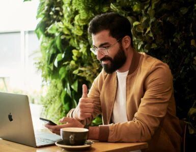 Homem sentado com um notebook e um café ao lado, ao longo do processo de avaliação de desempenho à distância