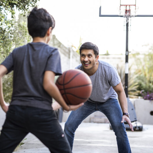 Man plays basketball with young son