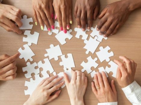 Multiple hands building a jigsaw
