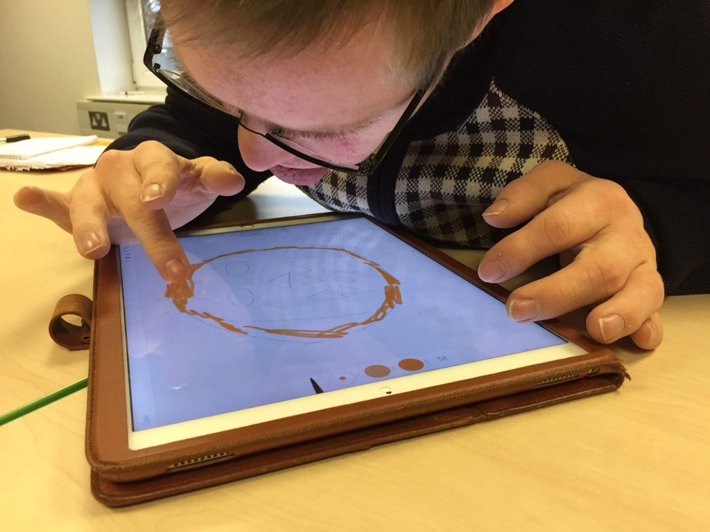 Image: a learner concentrating on drawing a picture on a tablet computer