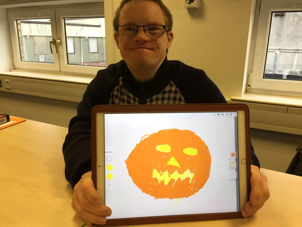 Image : a smiling learner holding up his tablet with his drawing of a Halloween pumpkin