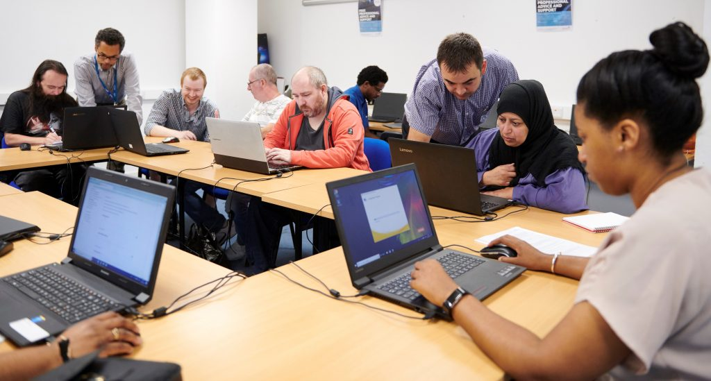 Image: Photo illustrating atmosphere of Digital Champion employment support - Several people in a training room working at laptops being showed how to use them