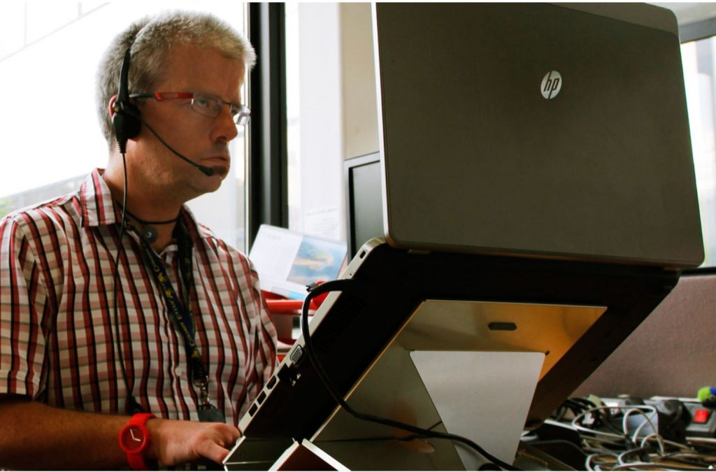 Image: Photo of a man using a laptop on a stand & wearing headphones with speaker