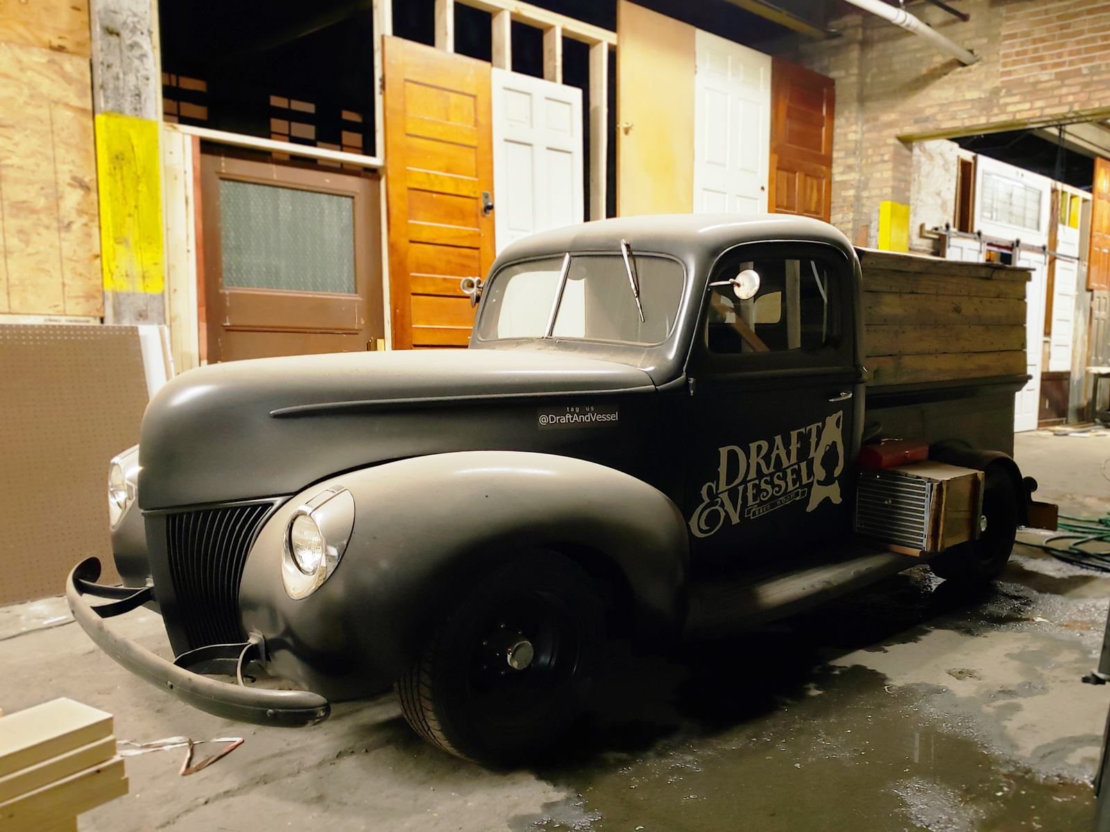 An vintage truck painted with the Draft and Vessel logo.