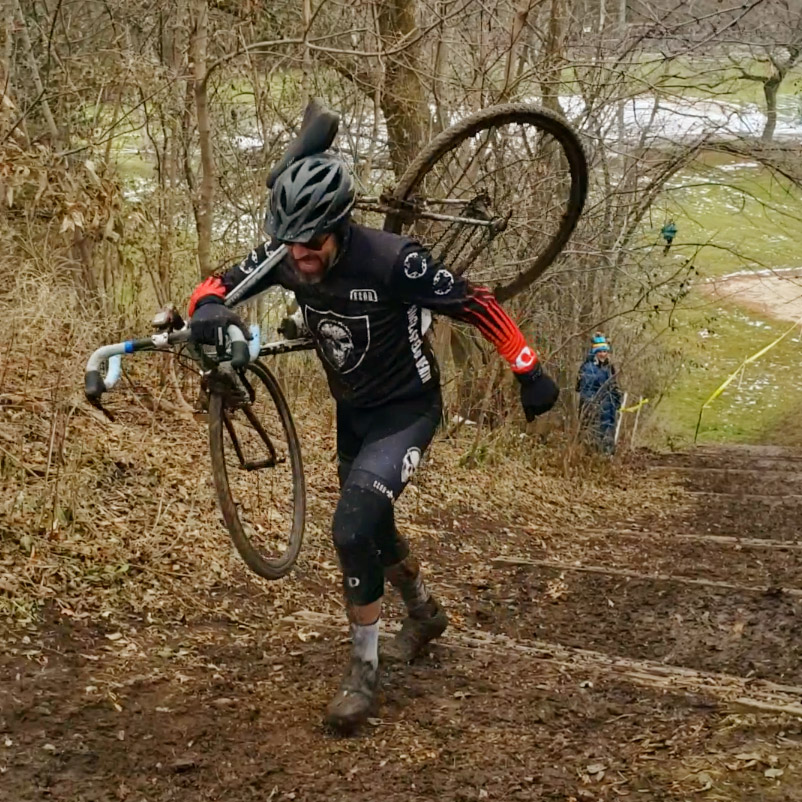 Man shouldering a cyclocross bike up some muddy park stairs in Oshkosh, WI