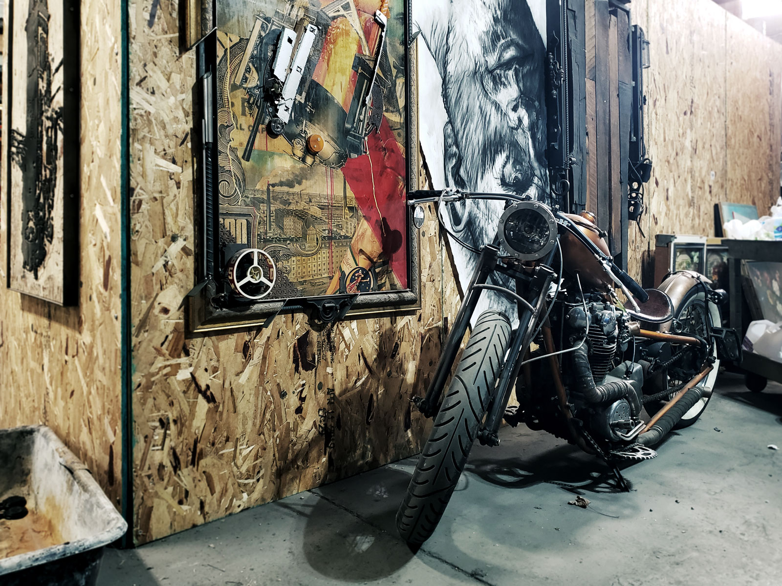 A motorcycle parked next to the industrial prints of Brandon Minga.