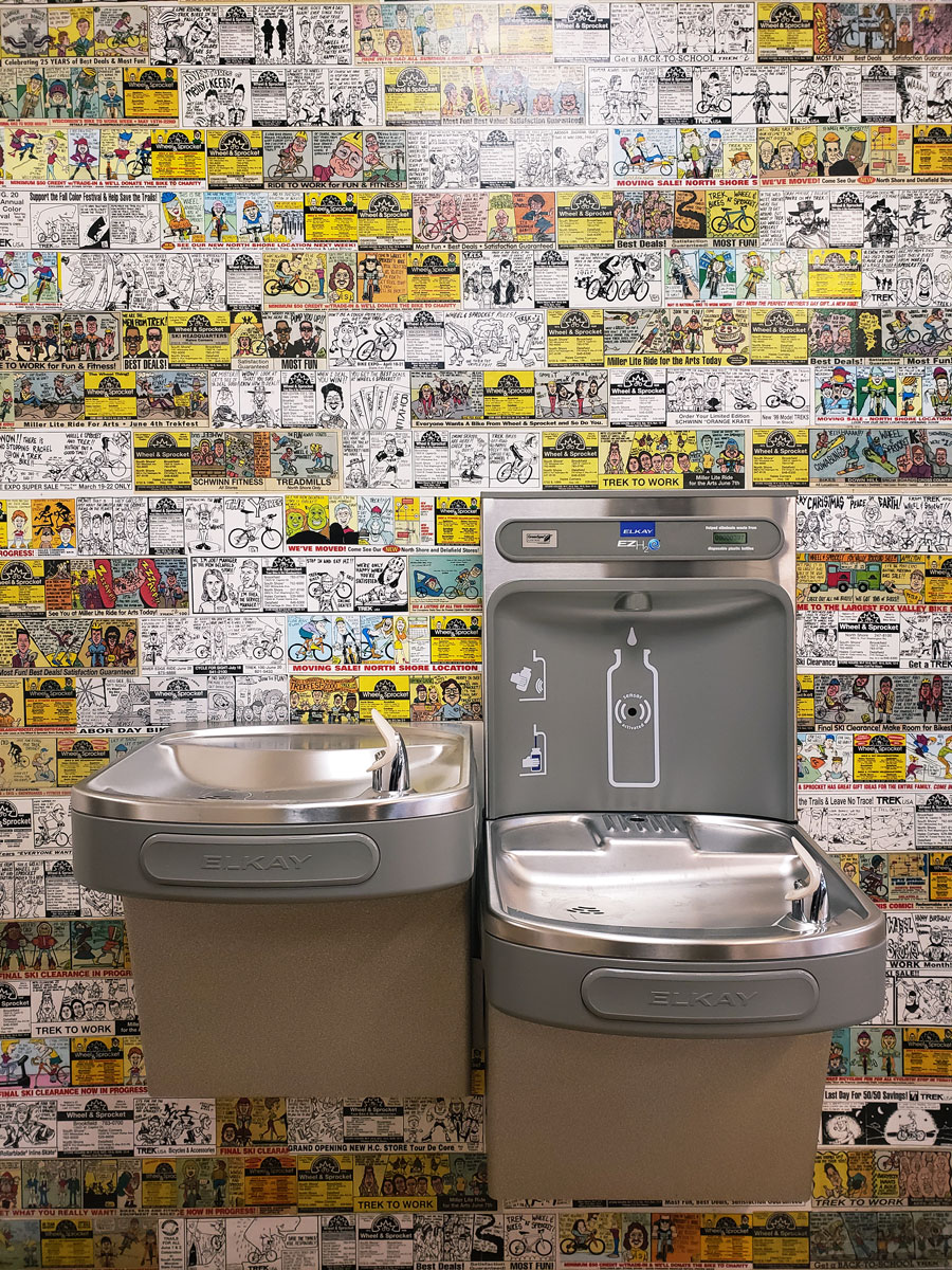 Drinking fountains installed against vintage Wheel & Sprocket newspaper comics.