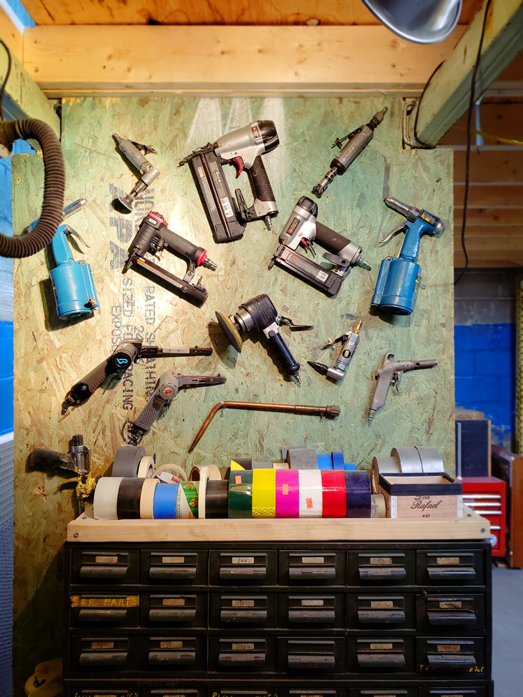 Power tools arranged artfully on a peg board sit above organizational drawers.