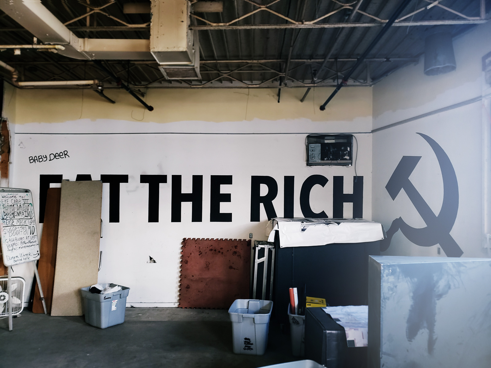 A wall with a mural proclaiming 'Eat the rich' followed by a communist icon.