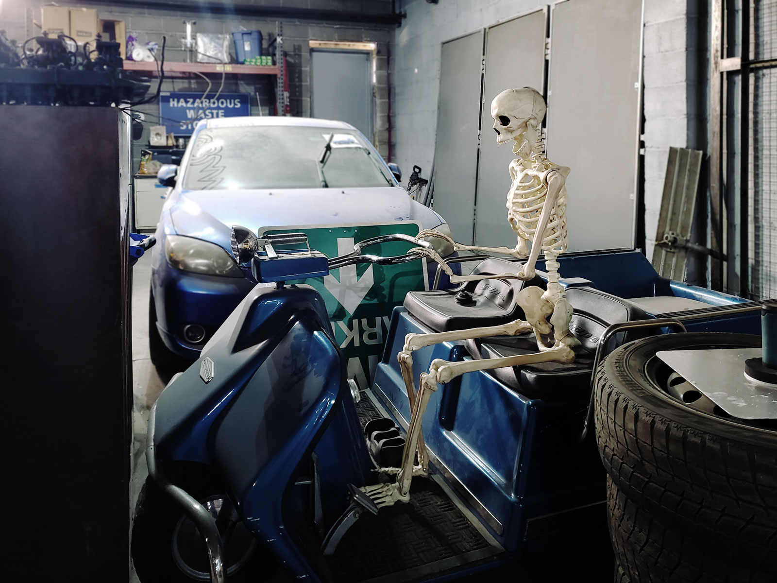 A skeleton riding a scooter.