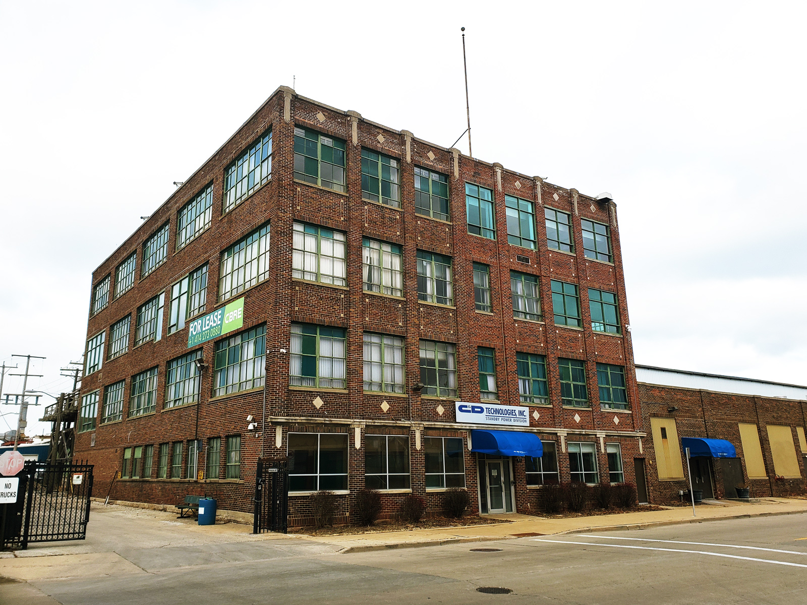 The main building at 900 E Keefe Ave. is a classic example of 1920's industrial red brick architecture.