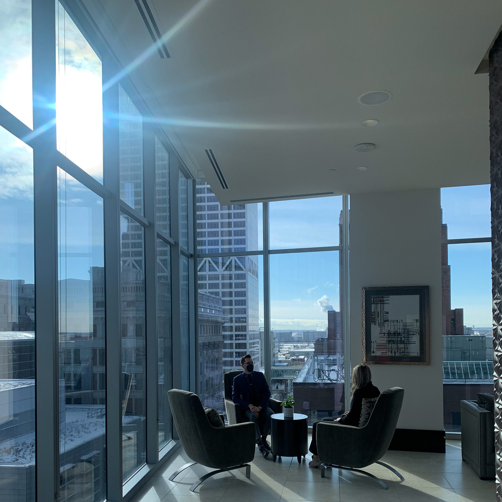 Two residents sit near wall-to-ceiling windows in the common area of the 7SEVENTY7 apartment building.