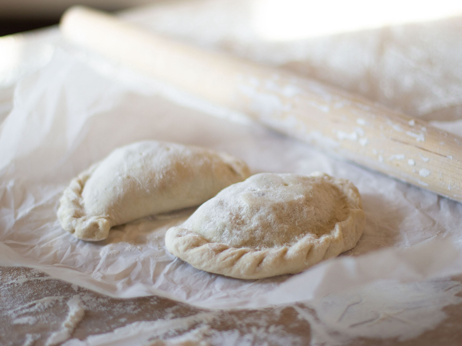Calzones in flour with rolling pin