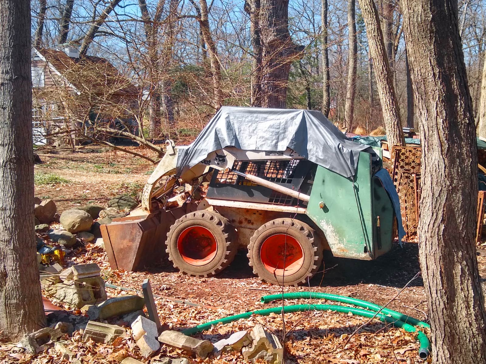 A small back hoe under a storage tarp on public trails.